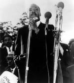 Martin Luther King, Jr. standing and speaking into a microphone.
