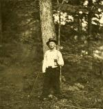 Image of Greeley in the woods holding an axe over his shoulder.