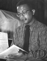 A head and shoulders portrait of William Strayhorn reviewing sheet music.