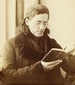 Sepia image of a man with shoulder length hair, wearing spectacles, and holding a book.