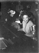 Mary Lou Williams seated at a piano and smiling into the camera. Visible behind are bar patrons.