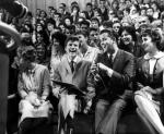 A young Dick Clark is seated in the front row of an audience of young people, next to a smiling Bobby Rydell.