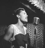 Billie Holiday singing into a microphone on stage.