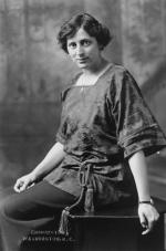 Formal portrait, three-quarter-length, seated, Crystal Eastman Benedict, facing left with upper body and head turned toward camera, wearing square-necked blouse cinched at waist with tasseled-rope belt, watch on left wrist, and necklace.