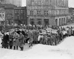A large group of men carrying musical instruments and placards march through the snow and up the steps of the Capitol.
