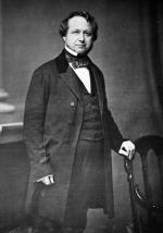 Black and white image of a man in a formal suit, standing, posing for this photograph.