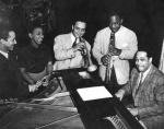 Duke Ellington is seated at a piano, surrounded by other musicians and fans.