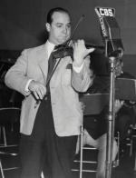 Joe Venuti, in a suit, playing a violin in front of a microphone.