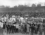 Rally to Authorize a Strike. Front View of Large Crowd at Turtle Creek Stadium on Lynn Avenue in Turtle Creek Pennsylvania. Workers Hold Signs Asking for a $2 a Day Increase. Published in the UE News December 3, 1945