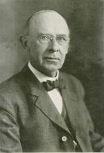 Black and white, head and shoulders photograph of a balding man, wearing a suit, shirt, and bowtie.