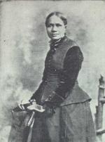 Portrait of an African -American woman standing with her hands on the back of chair.