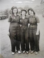 Three women pose for this photo.'