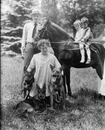 Family photo. Two small children sit in a saddle atop a horse. Mrs. Pinchot kneels and pets three german shephard dogs. Pinchot stands at the horse's head.