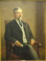 Oil on canvas of a bearded man, seated and wearing a suit.
