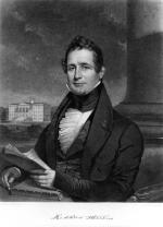 A man in formal dress is seated.