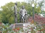A bronze statue of a man seated and a young boy standing next to him, with one hand outstretched and the other holding a cap. The statue is on a platform and is surrounded by landscaping.