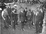 This photo shows that committee of men, dressed in suits, and one woman in overalls, entering a mine.