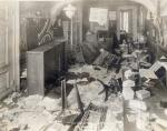 Image of an office that has been searched and items thrown on the floor and furniture overturned