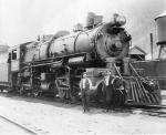 A large locomotive sits on a track and two men pose along its side.