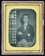 Daguerreotype of a man with mutton chop whiskers, bow tie. Jail door in background.