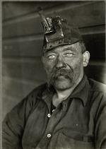 Head and shoulders of a miner covered it soot and wearing a miners hat with light.