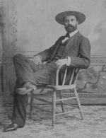 Owen Wister wearing western wear and sitting in a chair.