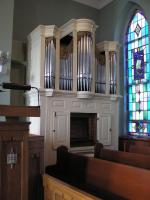 Image of organ inside a church. Pews are visible. A stain glass window is to the right of the organ.