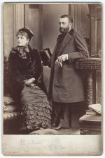 Sepia photograph of Mr. and Mrs. Henry Clay Frick.  He holds a top hat and gloves. She is wearing hat and is seated. Both are in formal dress.  Image taken in Boston in 1882.