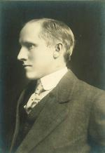 A man wearing a suit coat, vest, shirt, and tie. Side view, facing left, head and shoulders.