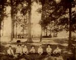 Photo of boys sitting under trees with baseball mitts and bats (circa 1890).