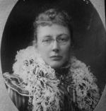Head and shoulders image of a woman wearing glasses and a feathered wrap