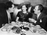 Three people are seated at a table are talking. A woman wearing a hat sits between the two men.