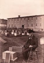 "Photograph of Lorenzo L. Langstroth, the ""Father of American Beekeeping, sitting in an apiary and holding a frame from his moveable frame beehive."