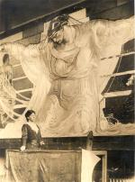 The artist stands on a scaffold in front of a portion of her 44-foot wide mural.