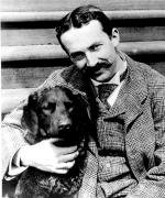 A black and white image of a dapper looking Mercer in a suit with his arm around a black dog.