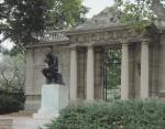 "Color image of the front of the Rodin Museum building, with the sculpture of the ""Thinker"" in the foreground"