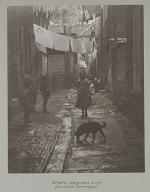 Slum area with photograph of a young children standing in an alleyway.