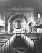 Interior photograph of the First Presbyterian Church depicting the pews and the altar. Behind the altar is a beautifully decorated wall with several arches.