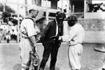 Umpire and player have a discussion while the catcher listens.