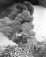 The switch to iron storage tanks did not eliminate the risk of fire. Here, the spectacle of an iron tank burning makes for an enjoyable outing for the townspeople. Tank fires would often last for several days.'