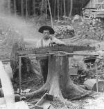 A worker filing a saw.'