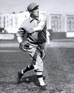 A portrait of Eddie Plank in uniform after just throwing the ball.