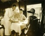 Black waiter dressed in a crisp, white uniform serves two well dressed, white passengers.
