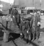 A young boy sits atop a railroad car full of large lumps of anthracite coal. Standing next to the car are his father and grandfather. All three are dirty from their work in the mines.