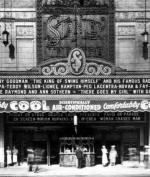An ornate theatre front with a large sign advertising Benny Goodman's band.