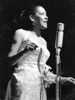 Billie Holiday is silhouetted on stage in a white dress against a black background.