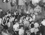 A black and white photograph of a group of people dancing in a room decorated with banners and balloons. Visible in the background is the host at a podium.