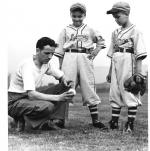 "Carl E. Stotz,  holding a baseball, posing with  Harold ""Major"" Gehron and Jimmy Gehron, two Little League ball players."
