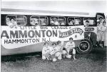 A black and white baseball card of the Hammonton New Jersey All star team bus. Four team members kneel beside the bus and other team members peer from each window and stand in the doorway.'