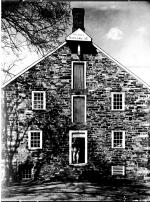 Black and white photograph of Stover Mill. A man is standing in the open doorway.